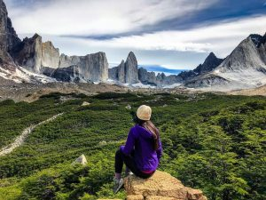 Viajera observando paisaje con bosque y montañas
