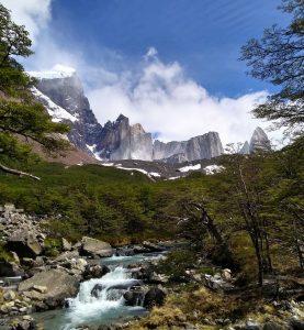Río y bosque con montañas de fondo