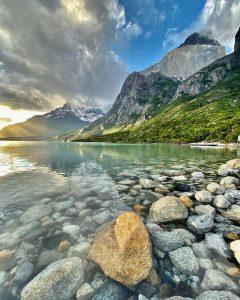 Lago cristalino con montañas y vegetación en el fondo en circuito w