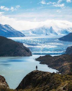 Persona observando inmenso glaciar y montañas