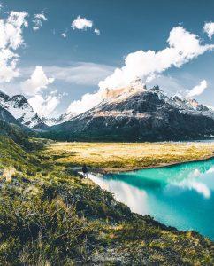 Lago color turquesa bajo grandes montañas